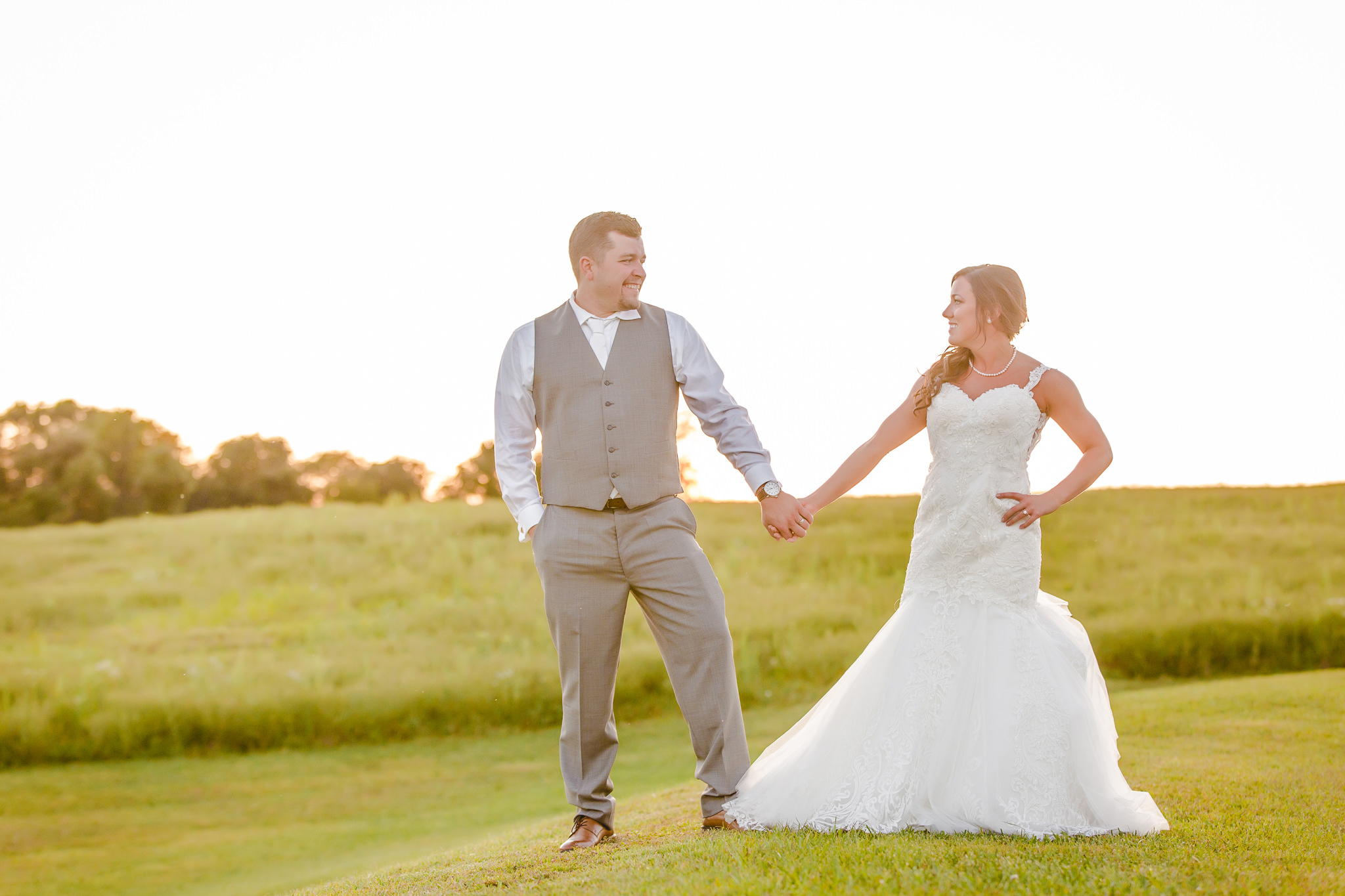 Bride and groom pose during golden hour at the White Barn