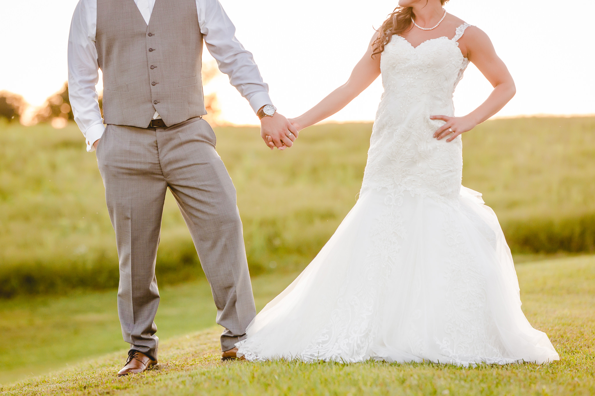Bride and groom hold hands during portraits at White Barn