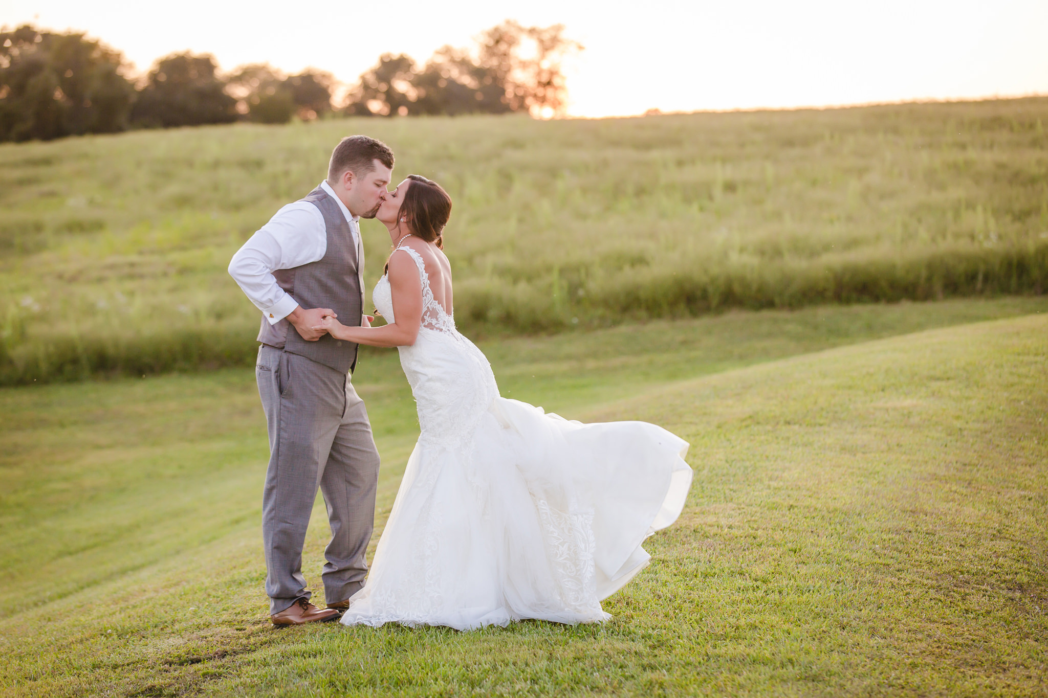 Bride and groom dance and kiss during portraits at their White Barn wedding