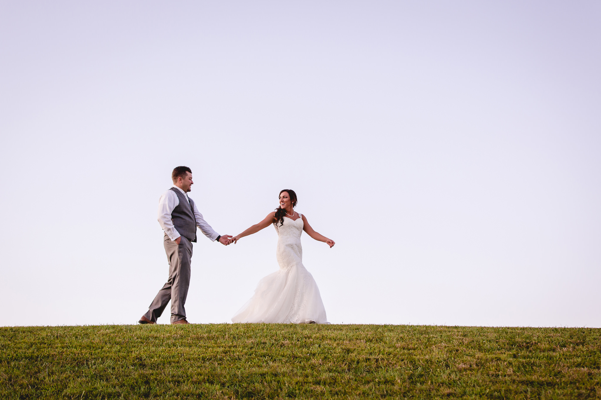 Bride and groom walk on top of a hill at White Barn
