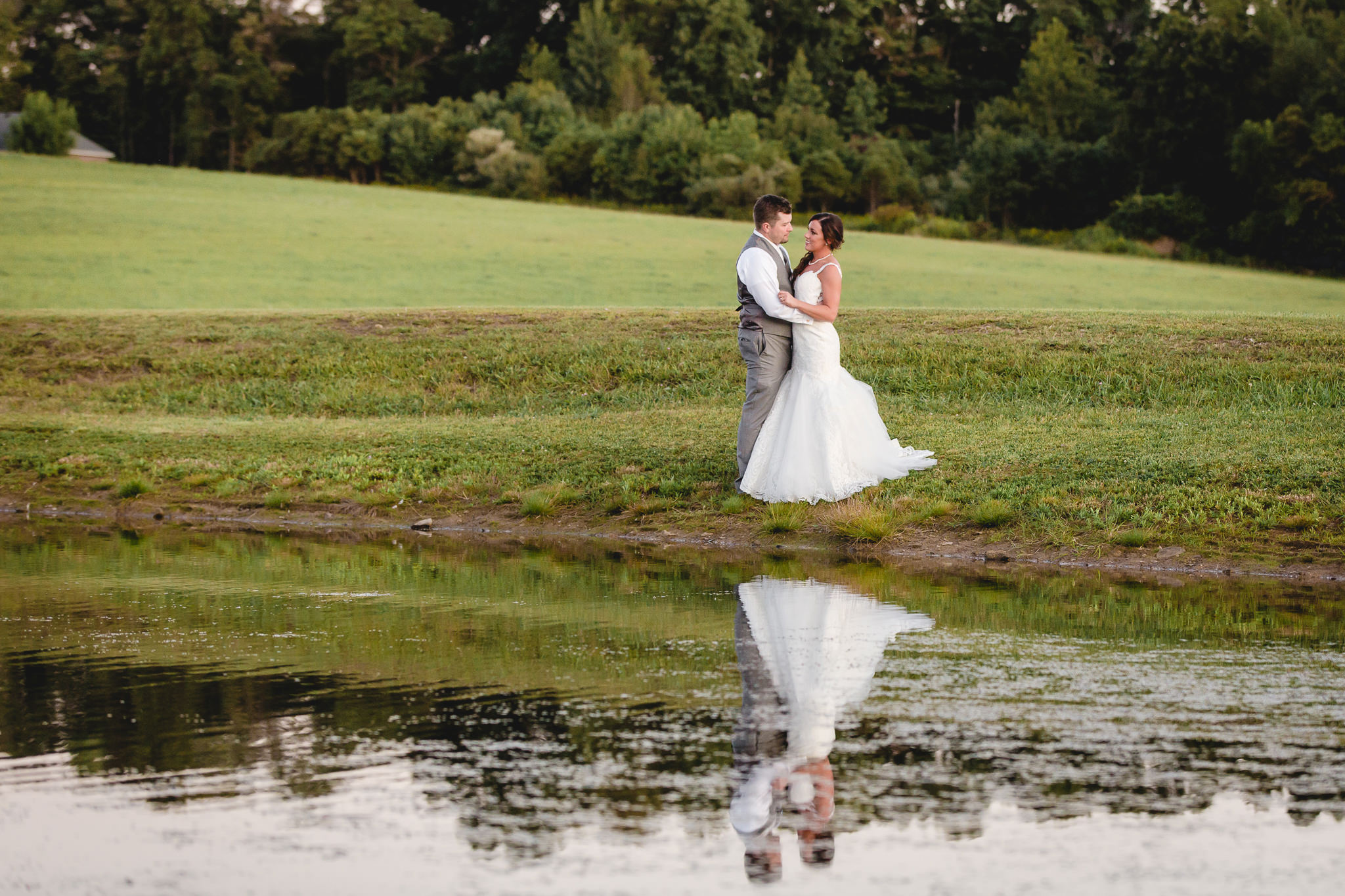 Bride and groom snuggle by the pond at White Barn