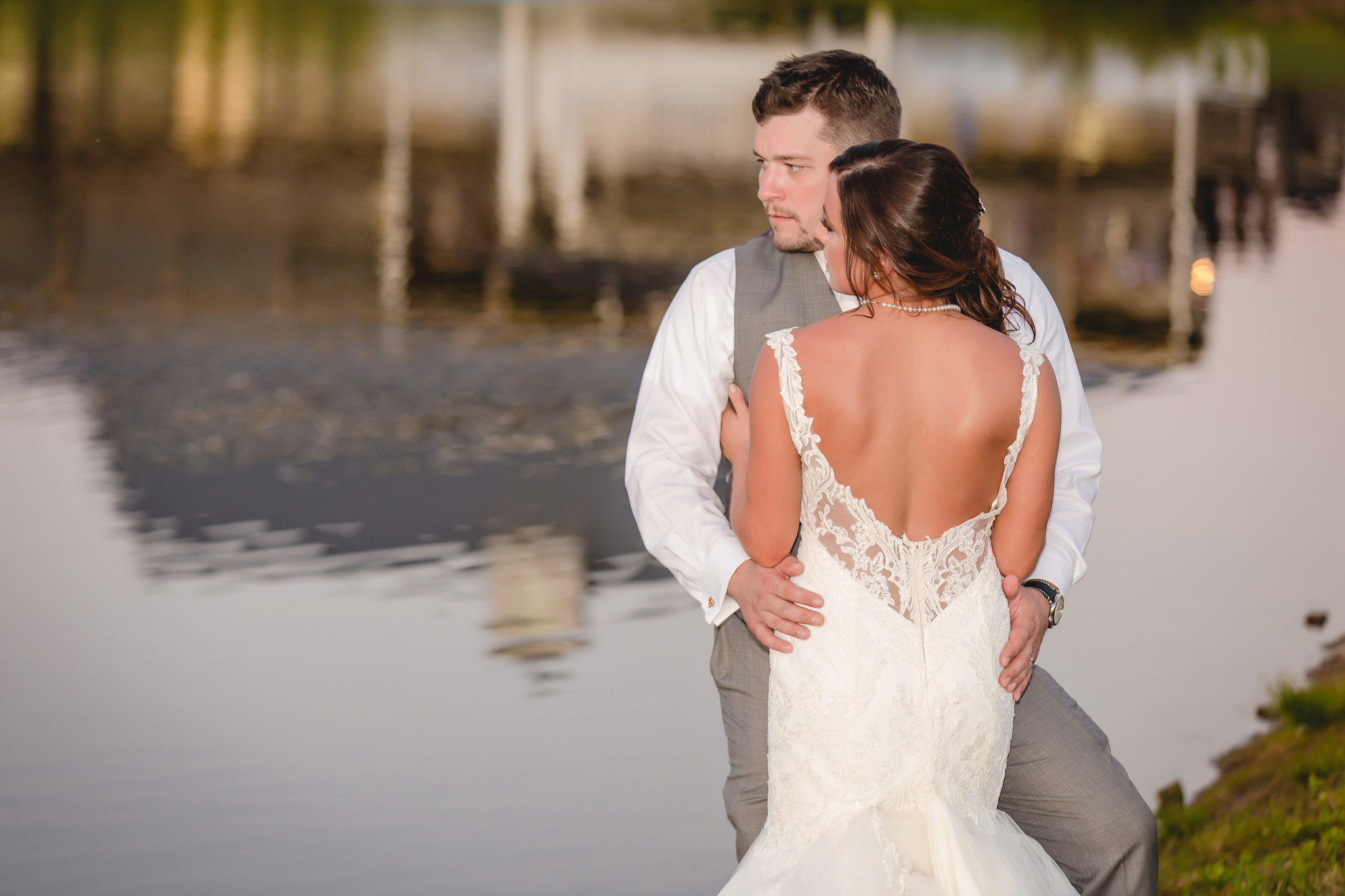 Bride and groom pose like models by a pond at White Barn