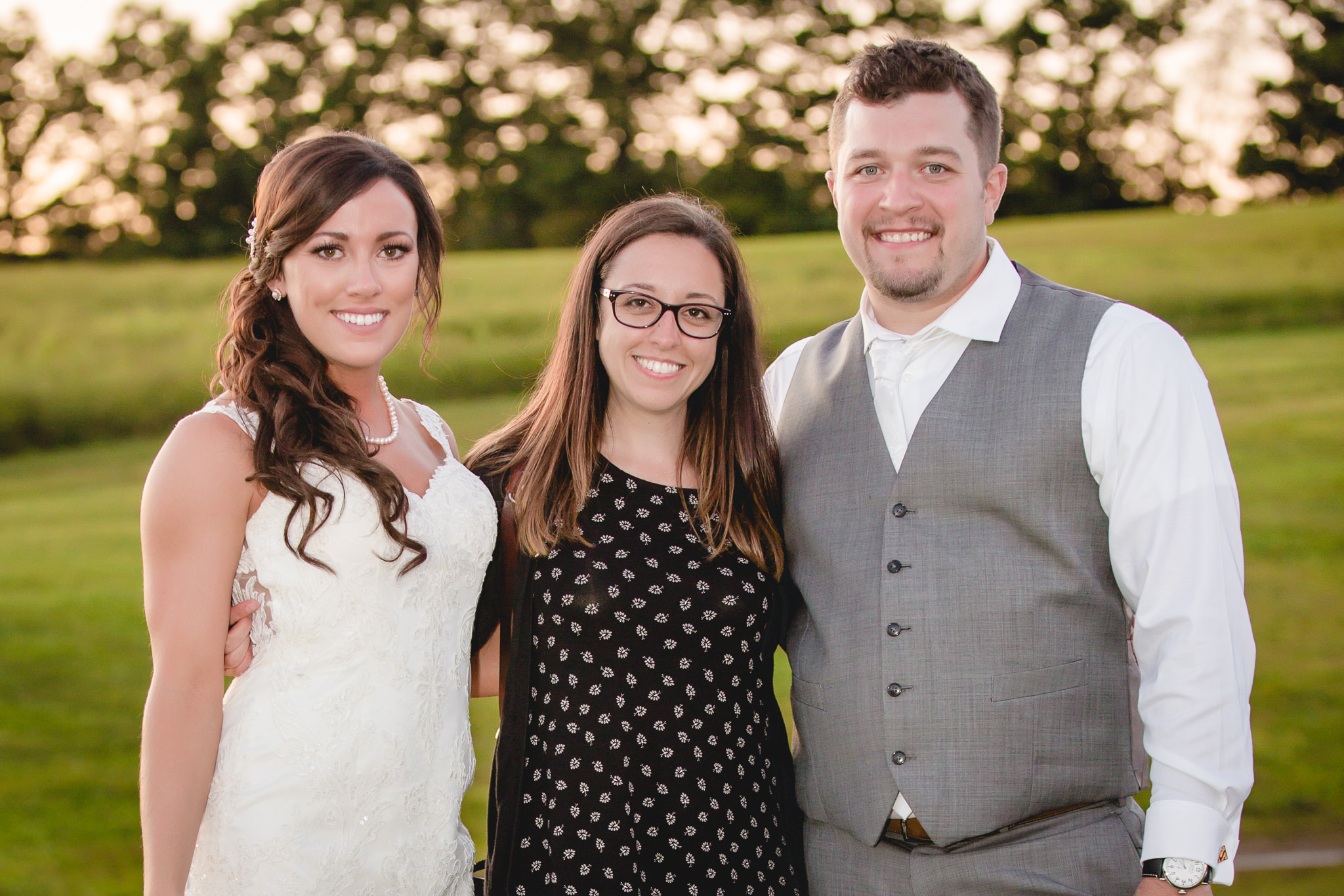 Bride and groom pose with their wedding photographer at White Barn