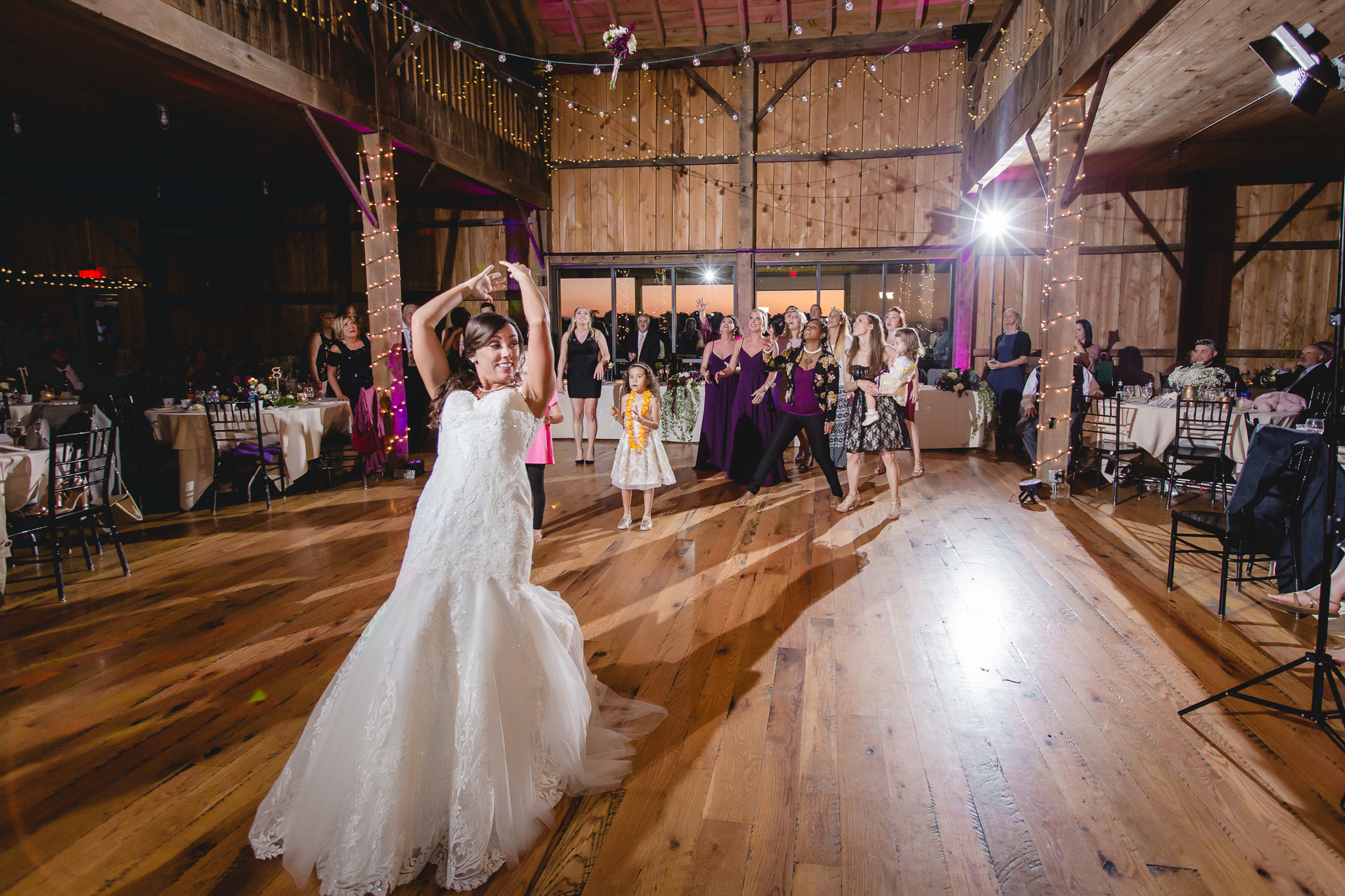 Bride tosses her bouqet at her White Barn wedding reception
