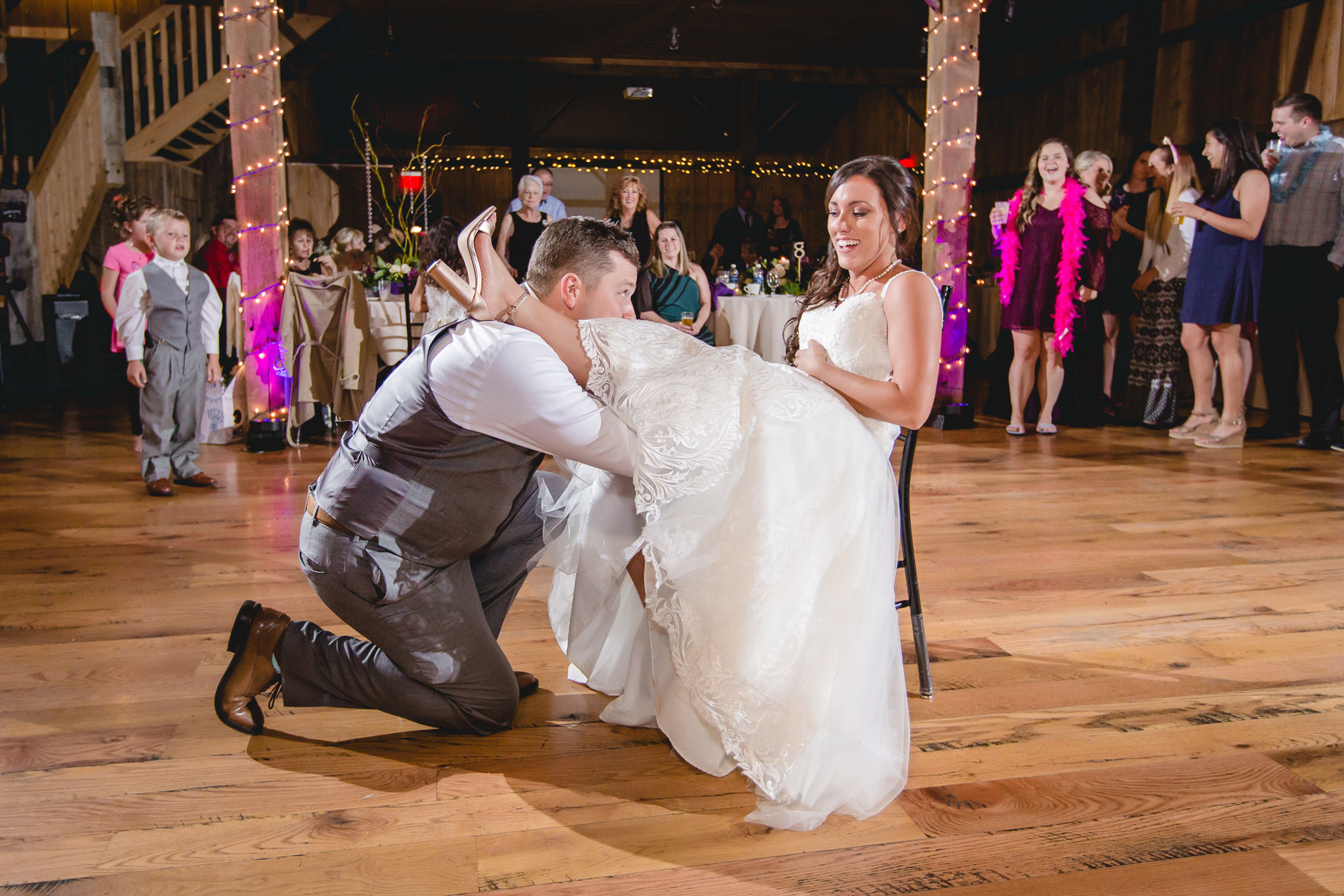Groom searches for bride's garter at their White Barn wedding