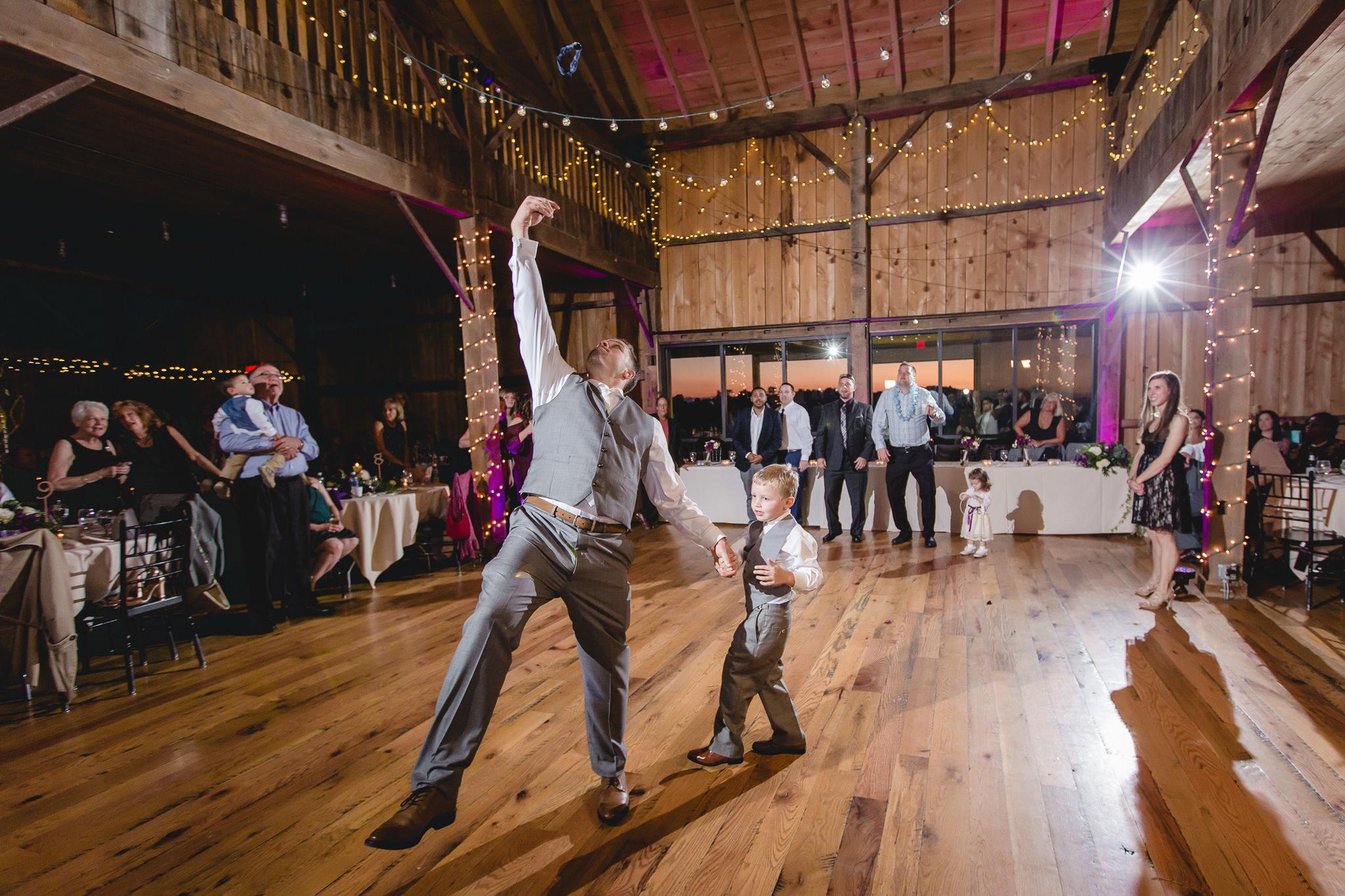 Groom tosses the garter at a White Barn wedding