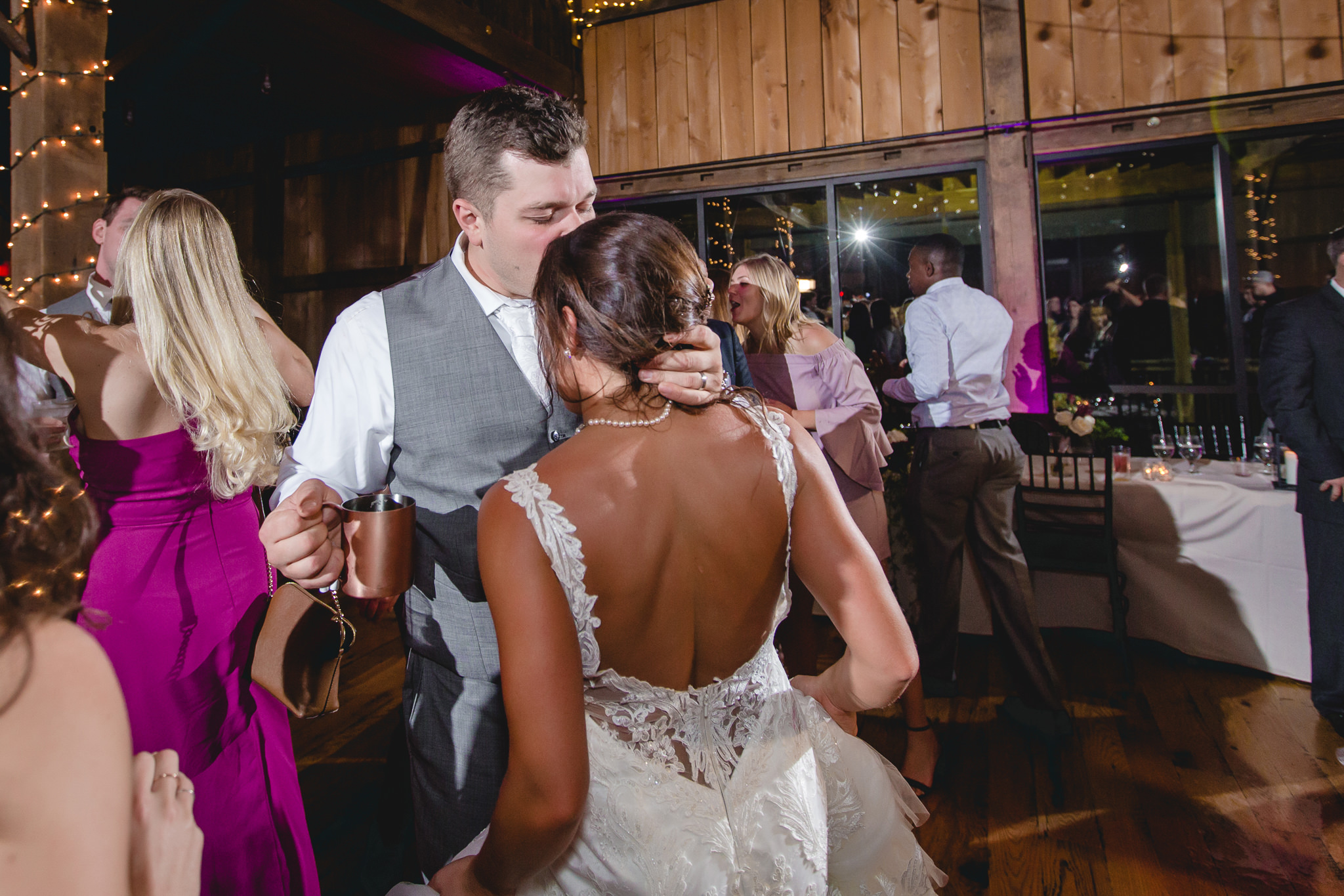 Groom kisses his bride's head at White Barn