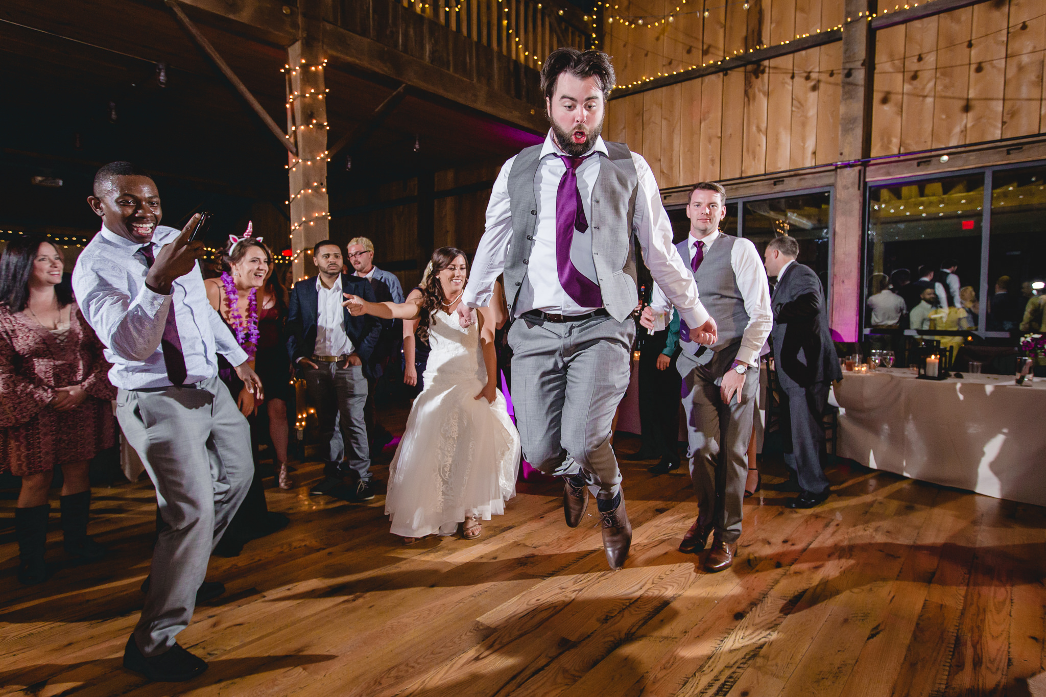 Best man leaps in the air while dancing at the White Barn