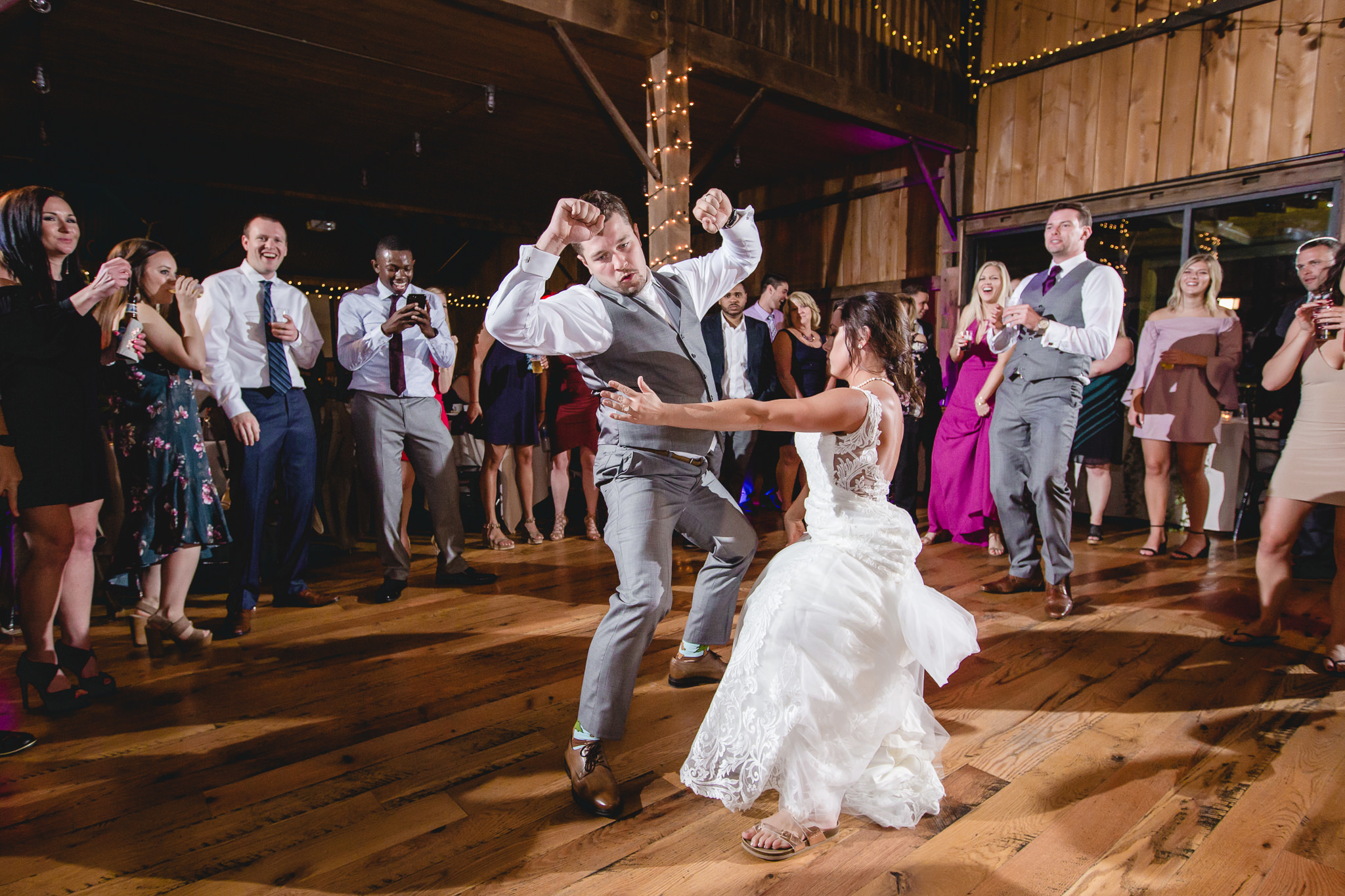 Groom dances with his bride and guests at White Barn
