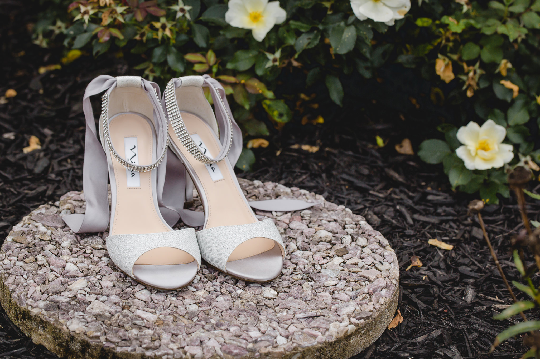 Bridal shoes by Nina rest on a rock before a wedding at the Fez