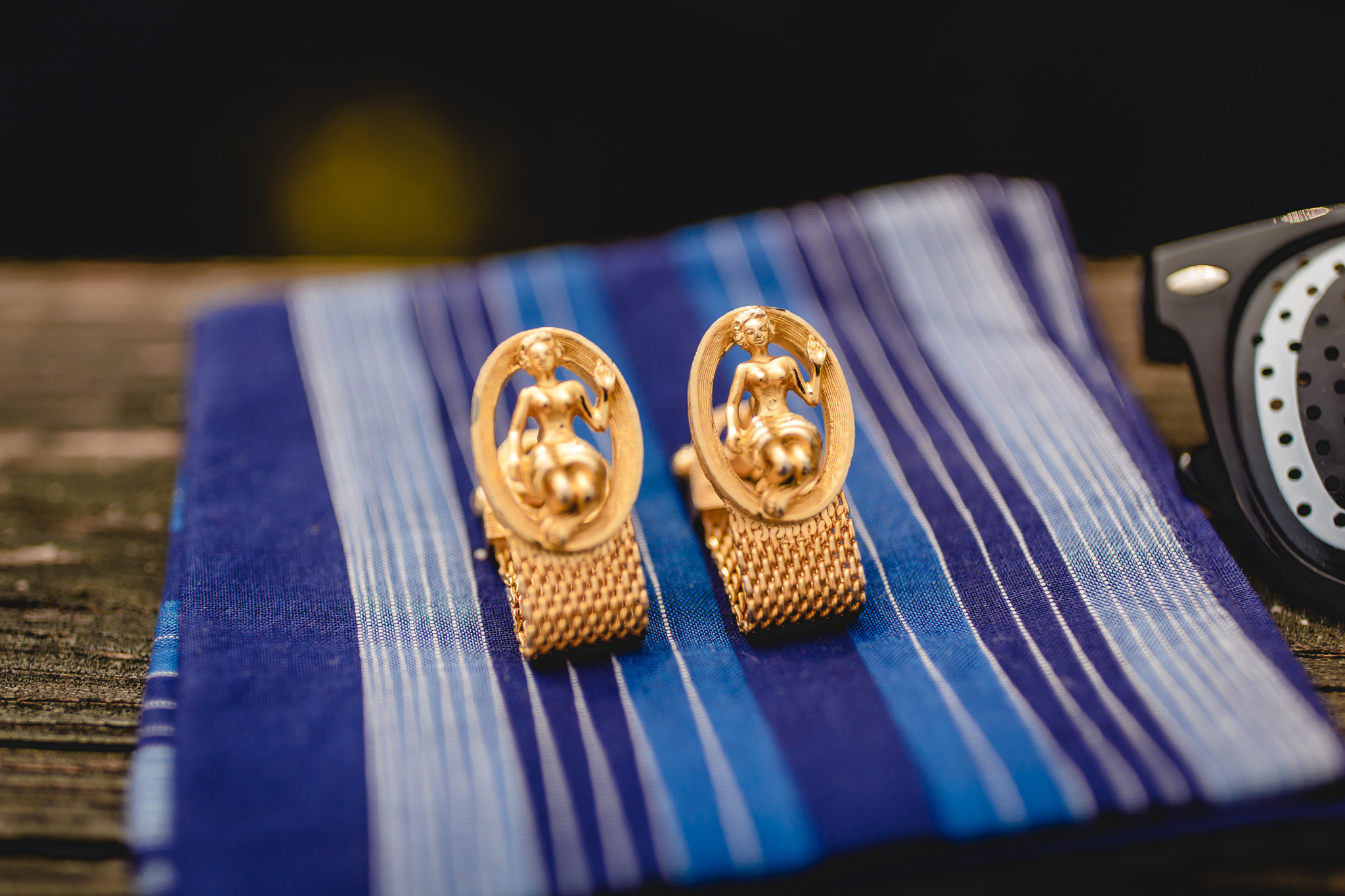Groom's gold cufflinks sit on his pocket square before his wedding at the Fez