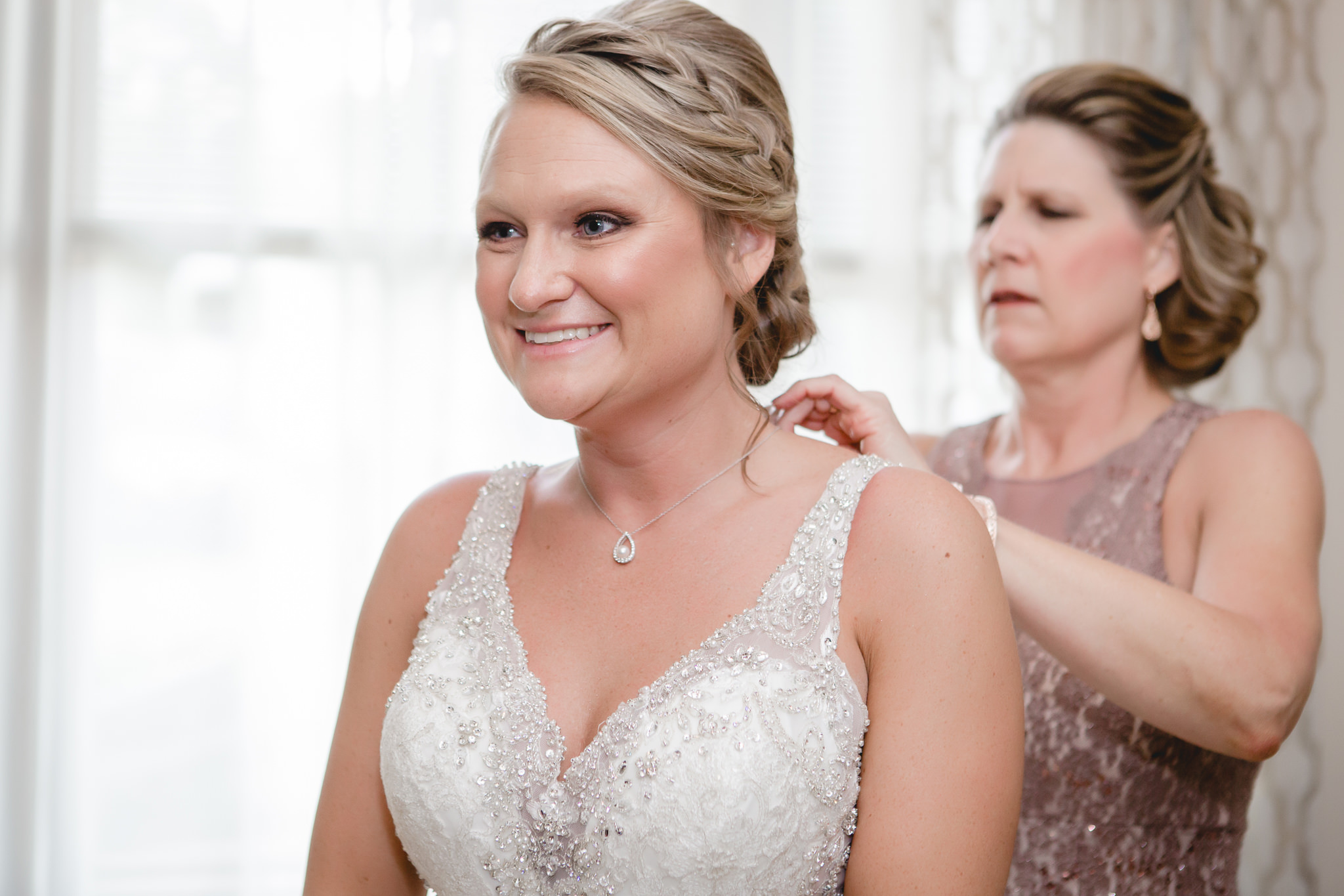 Bride's mom puts on her necklace before her wedding at the Fez