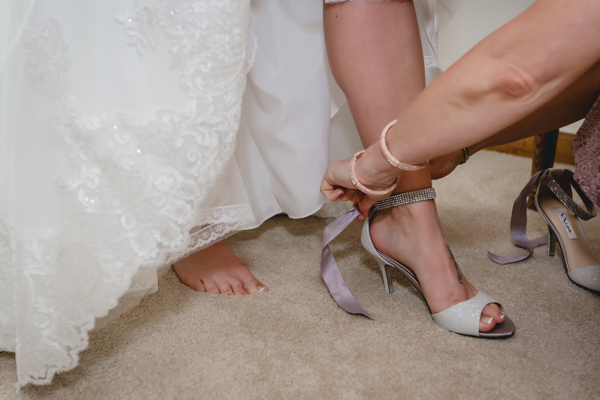 Bride's mom helps her into her shoes before her St. Titus Church wedding ceremony
