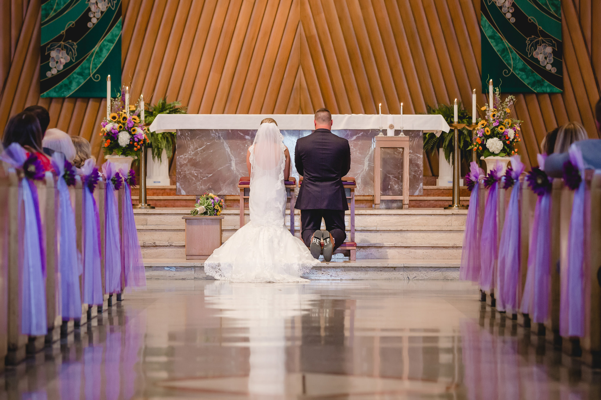 Bride and groom kneel at the altar of St. Titus Church