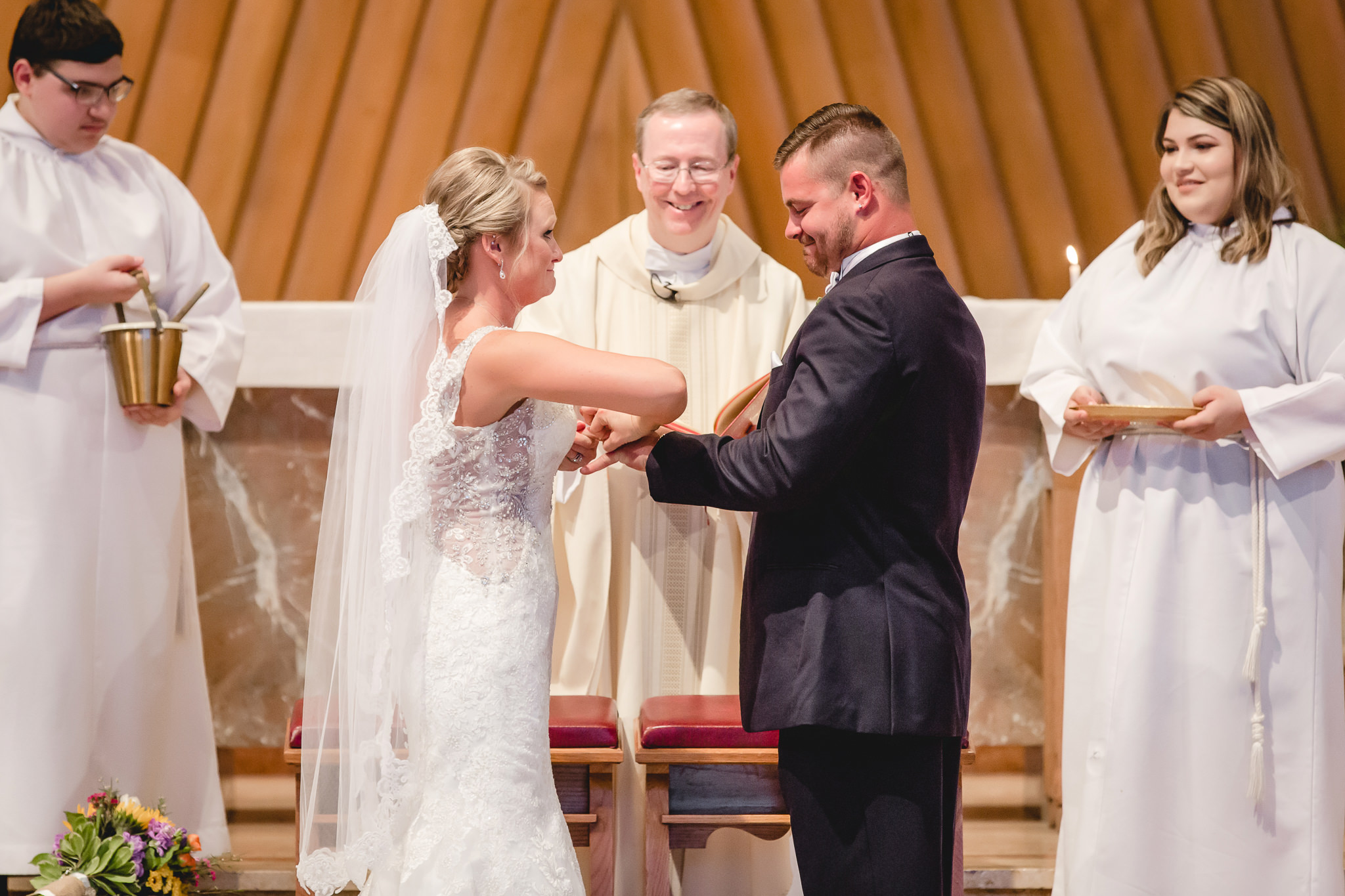 Bride struggles to get the groom's ring on his finger at St. Titus Church