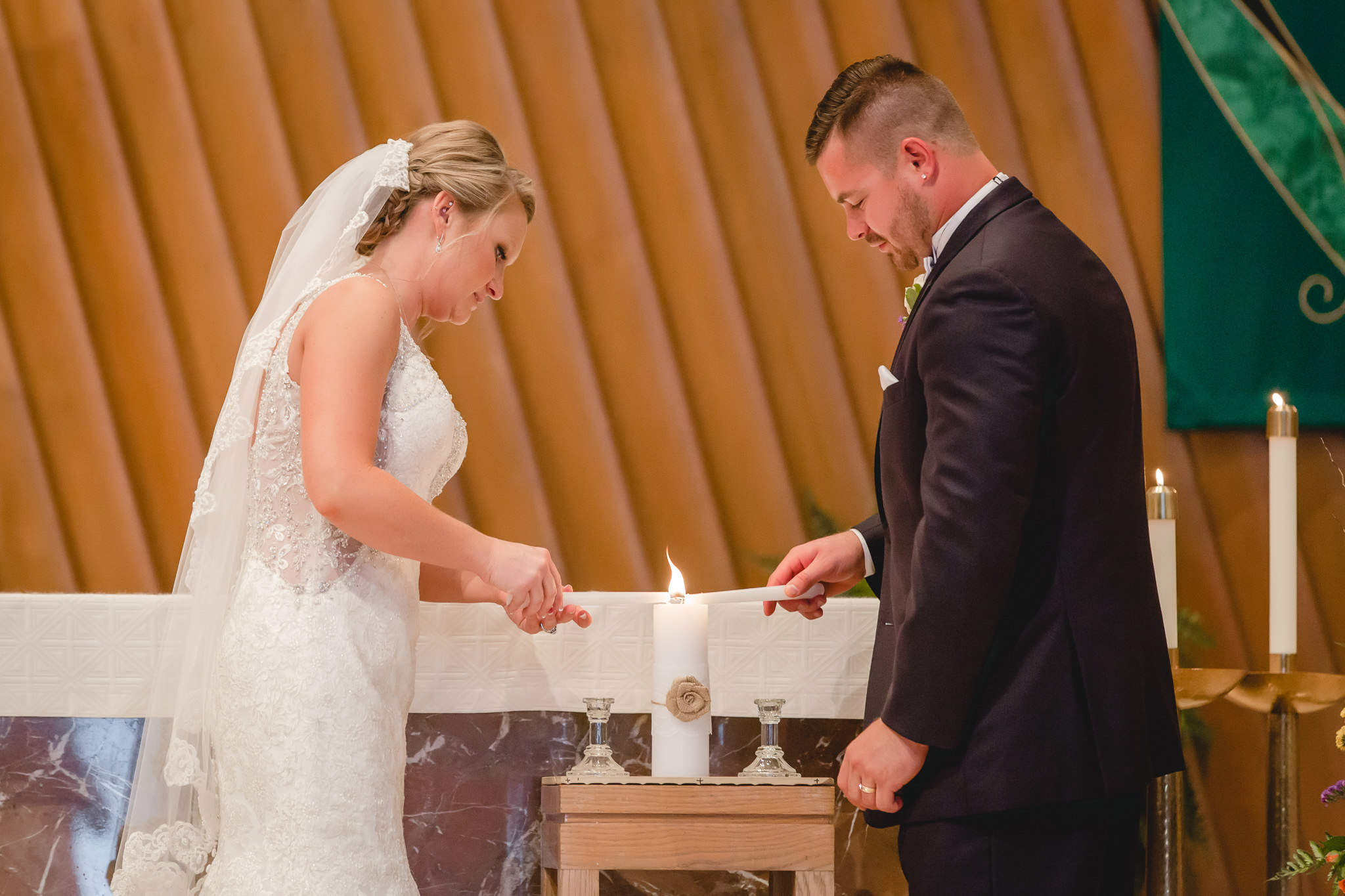 Bride and groom light the unity candle during their St. Titus Church wedding ceremony