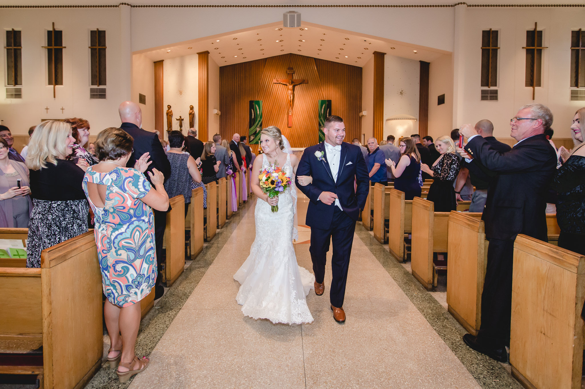 Bride and groom smile as they exit their St. Titus Church wedding ceremony