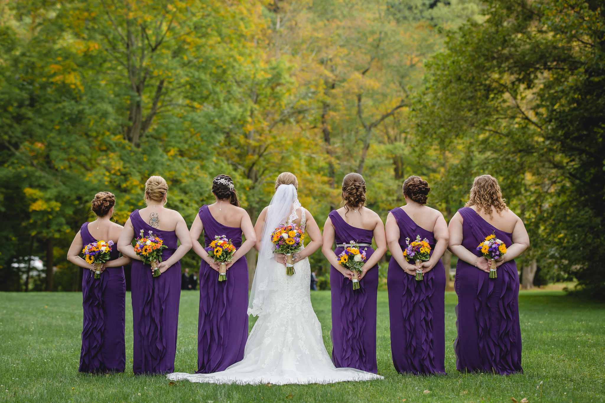 Bride and bridesmaids hold their bouquets by Patti's Petals Flower Shop
