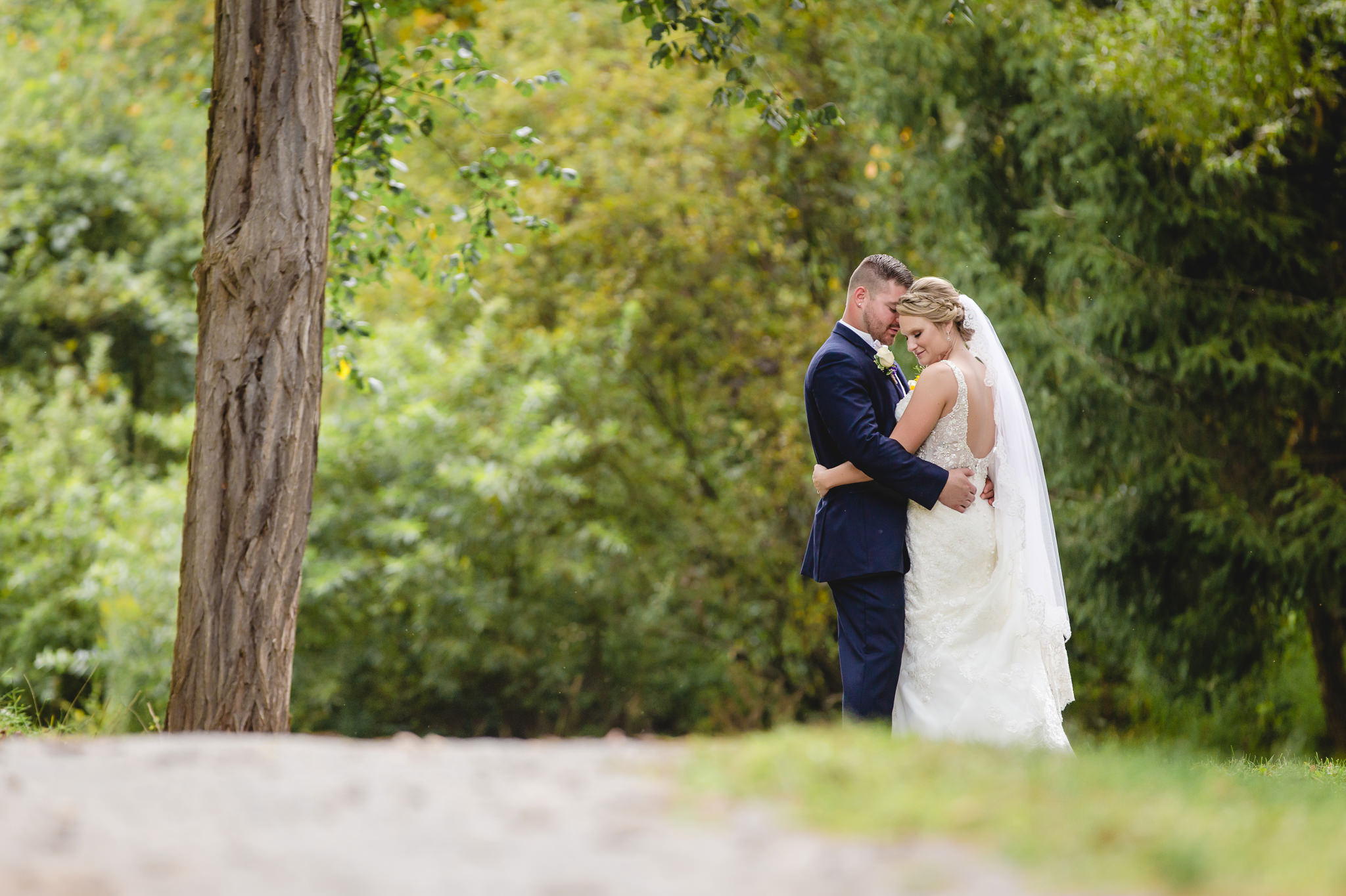 Newlyweds snuggle on a walking path in Moon Township
