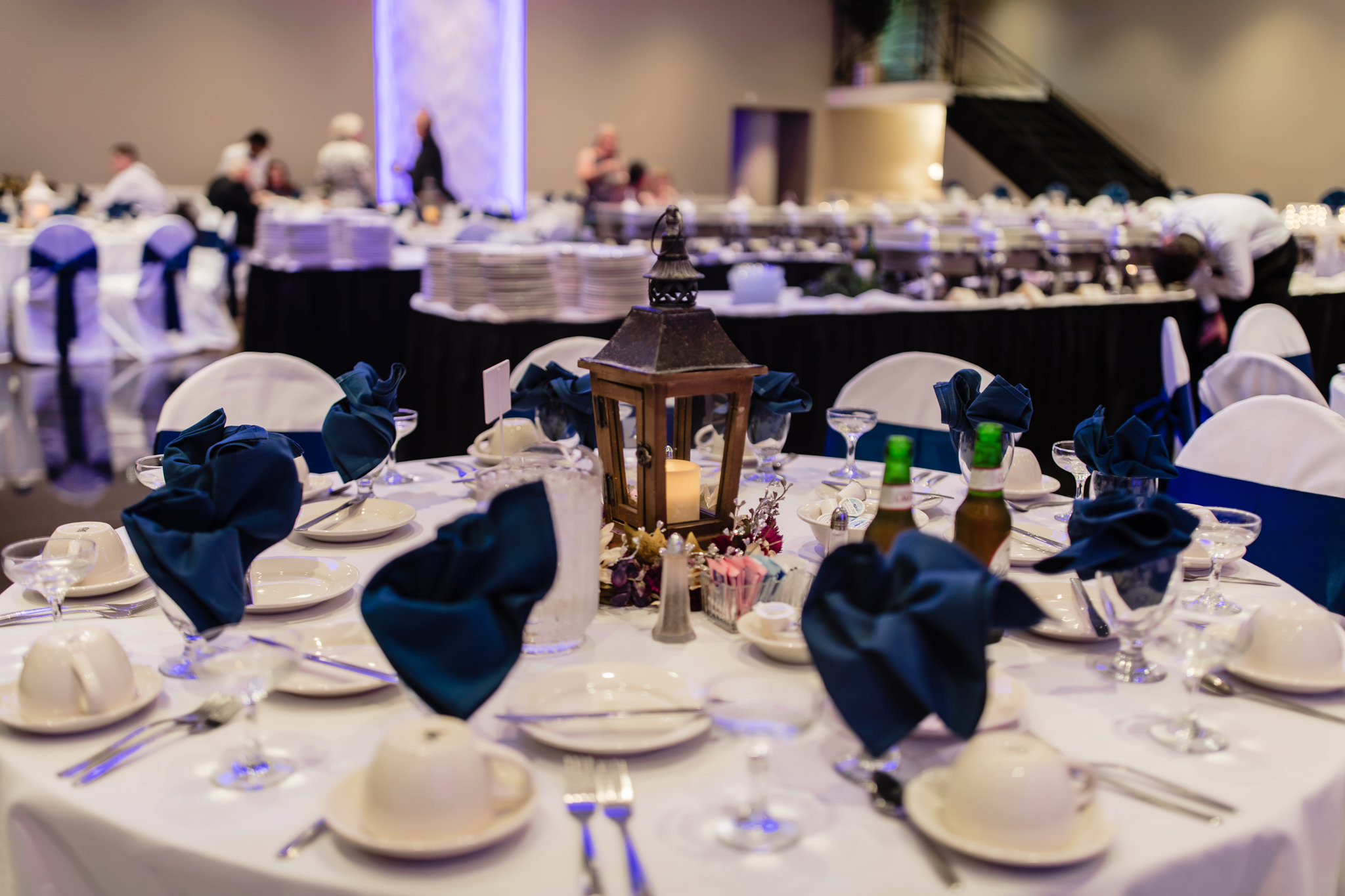 Lantern centerpieces with navy napkins setup for a wedding at the Fez