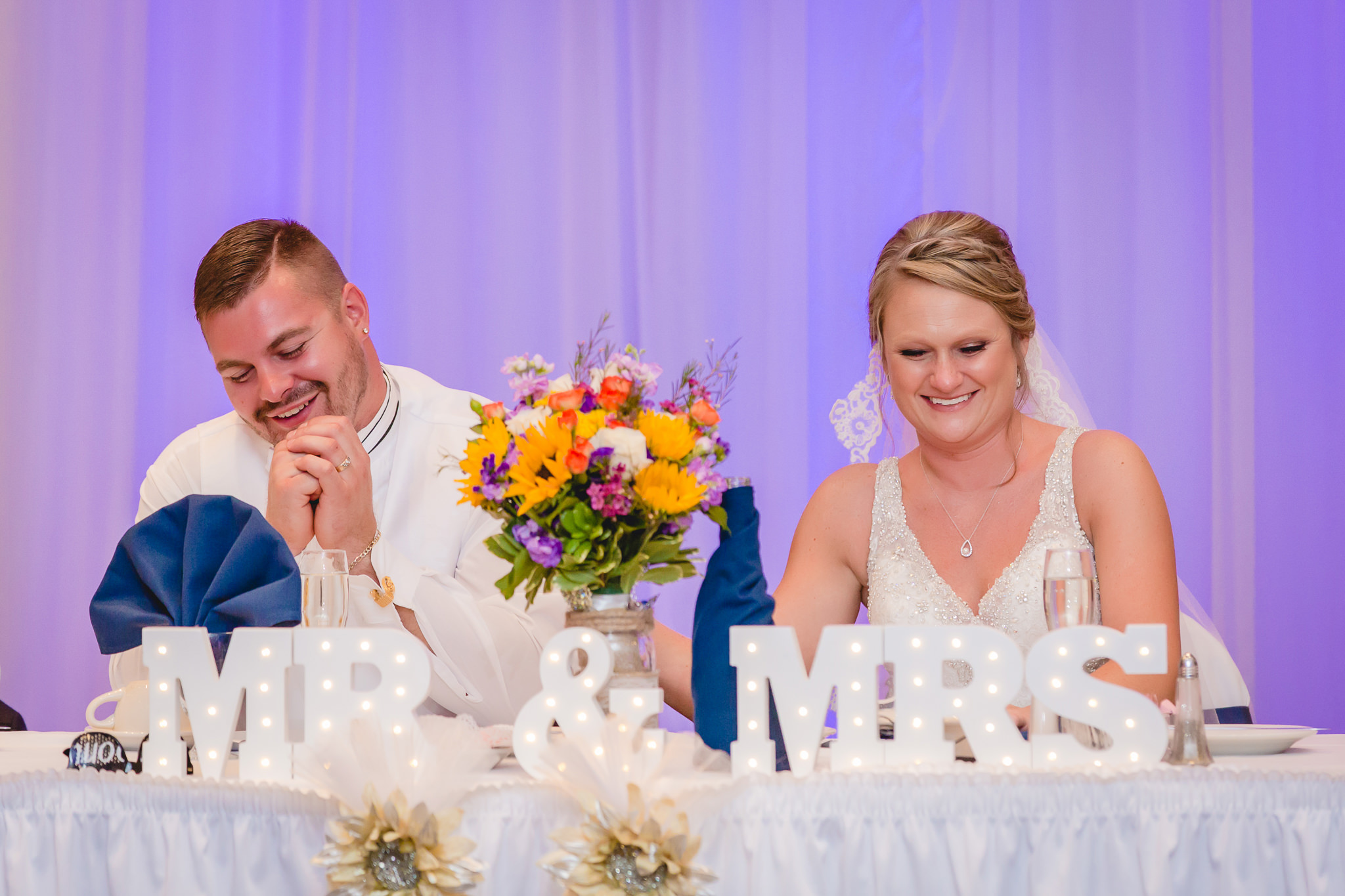 Bride and groom laugh during speeches at their reception at the Fez