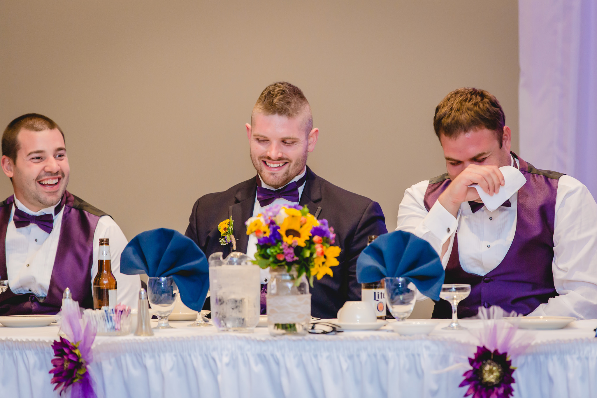 Groomsmen laugh during speeches at a Fez wedding reception