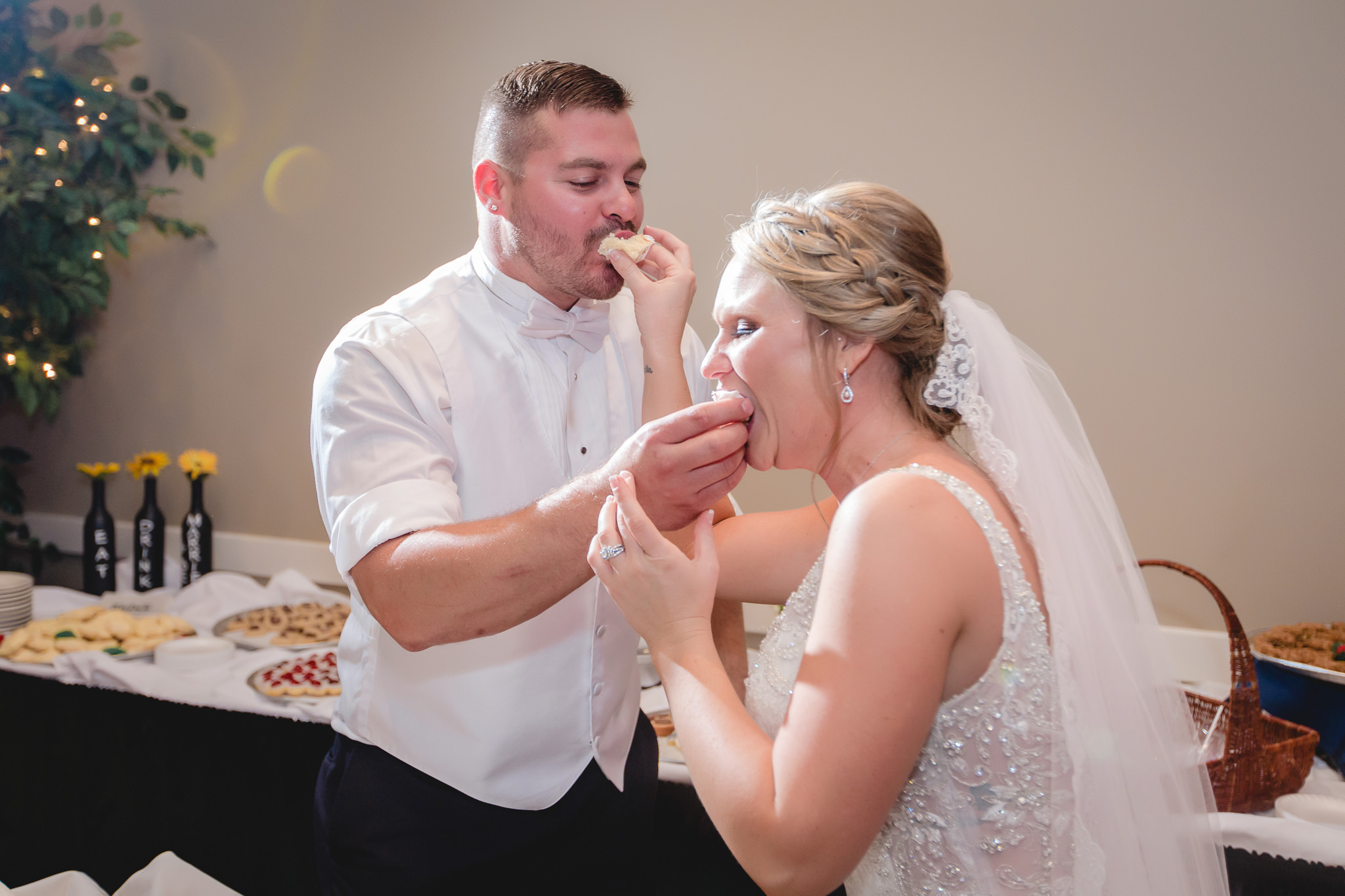 Bride and groom feed each other wedding cake at the Fez
