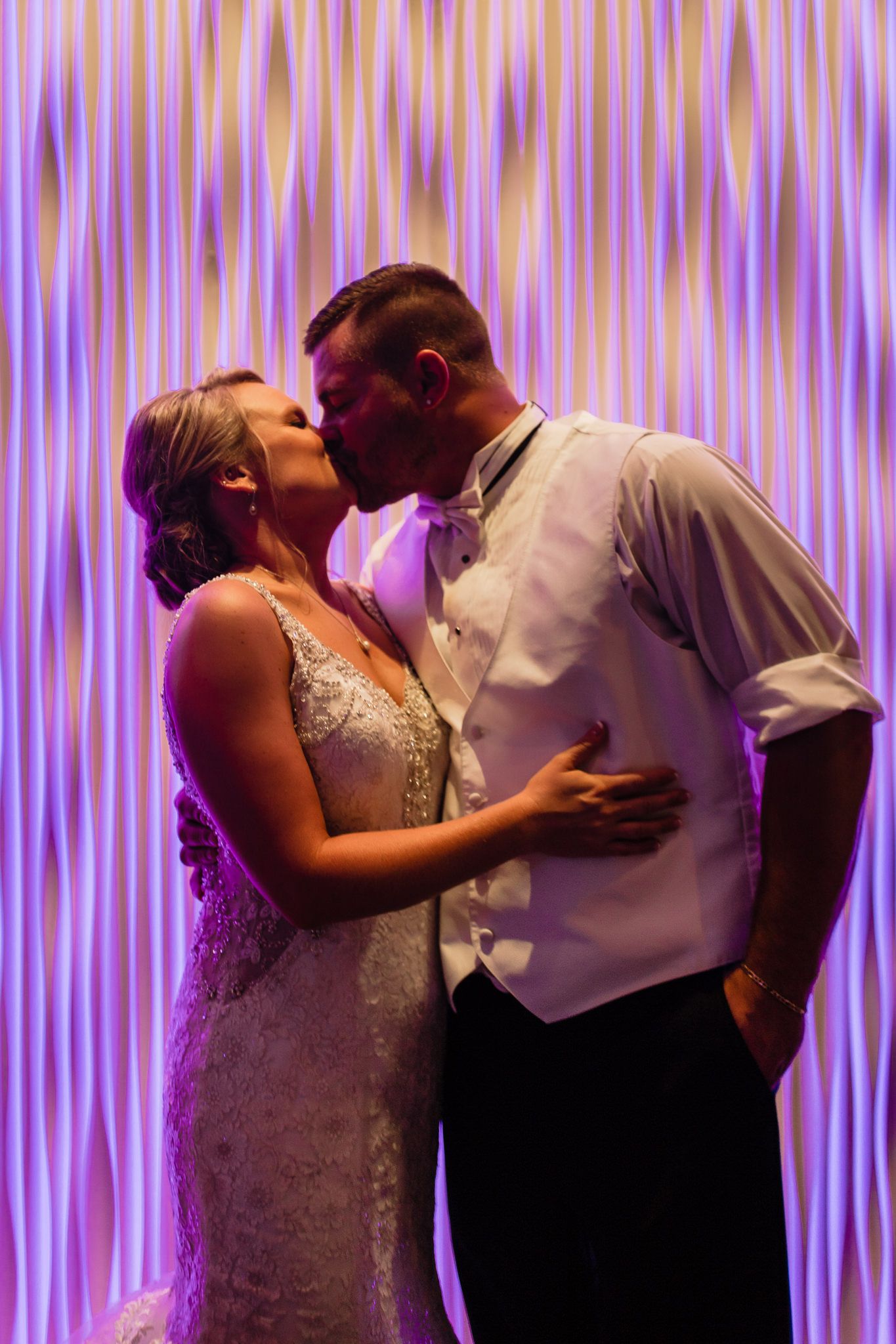 Bride and groom kiss against the light display at the Fez in Hopewell